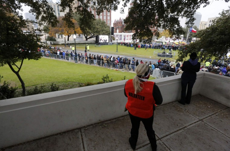 "An event volunteer and a spectator look down from atop Dealey Plaza's ""grassy knoll"" on the site where President John F. Kennedy was shot as crowds gather for commemorative ceremonies marking the 50th anniversary of JFK's assassination in Dallas, Texas November 22, 2013. (Jim Bourg/REUTERS)"