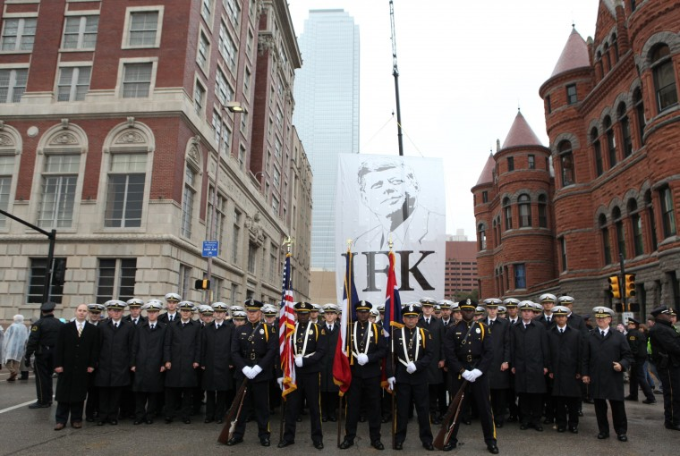 The Dallas Police Department Honorary Color Guard and the U.S. Naval Academy Men's Glee Club pose in front of a giant JFK banner after the conclusion of ceremonies marking the 50th anniversary of the assassination of President John F. Kennedy in Dallas, Texas November 22, 2013. (Jim Bourg/REUTERS)