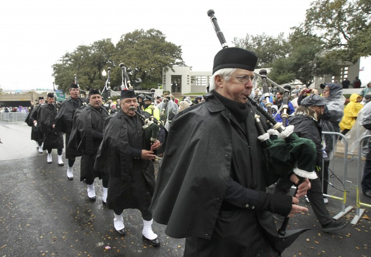 The Dallas Metro Police Pipes and Drums corps march up Elm Street where President John F. Kennedy was shot, at the conclusion of ceremonies marking the 50th anniversary of the assassination of President John F. Kennedy in Dallas, Texas November 22, 2013. (Jim Bourg/REUTERS)