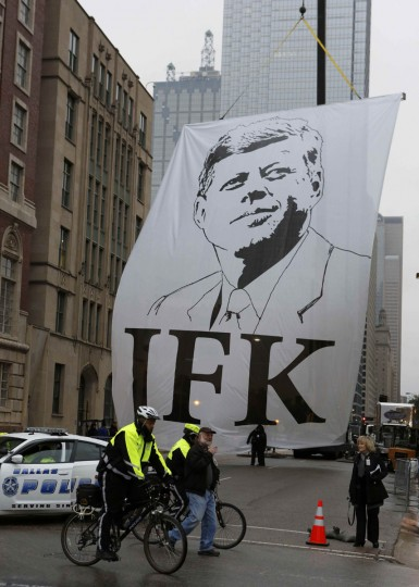 A banner of President John F. Kennedy is pulled into place as crowds gather in Dealey Plaza for commemorative ceremonies marking the 50th anniversary of JFK's assassination in Dallas, Texas November 22, 2013. (Jim Bourg/REUTERS)
