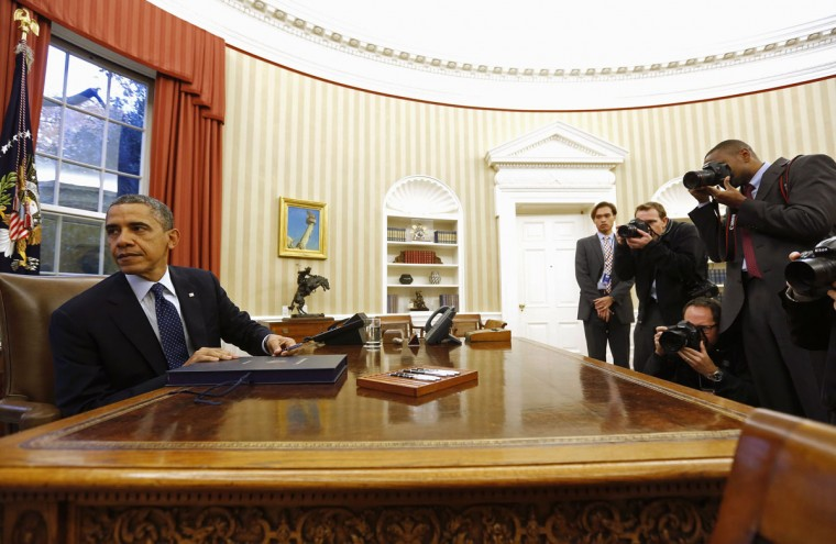 U.S. President Barack Obama turns away from the photographers after he signs a bill in the Oval Office of the White House in Washington, November 27, 2013. According to the White House, Obama signed three bills into law S. 252, H.R. 1848, and H.R. 3204. (REUTERS/Larry Downing)