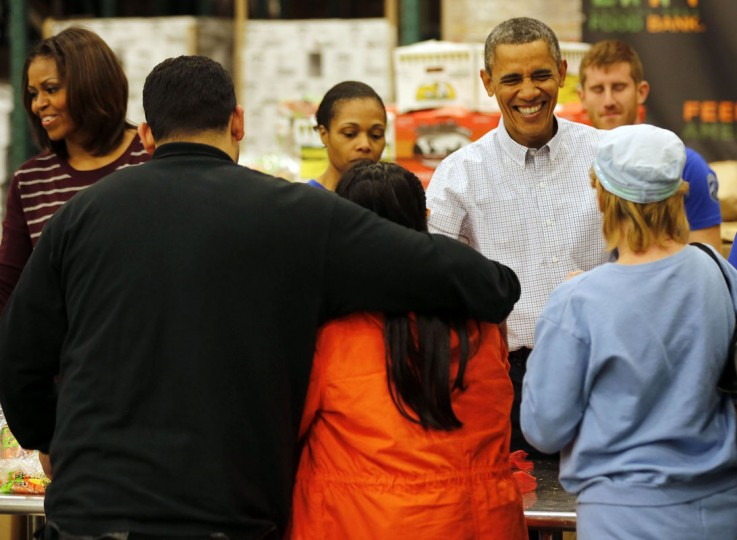 U.S. President Barack Obama smiles as he hands out Thanksgiving food with first lady Michelle Obama at the Capital Area Food Bank in Washington, November 27, 2013. (REUTERS/Larry Downing)