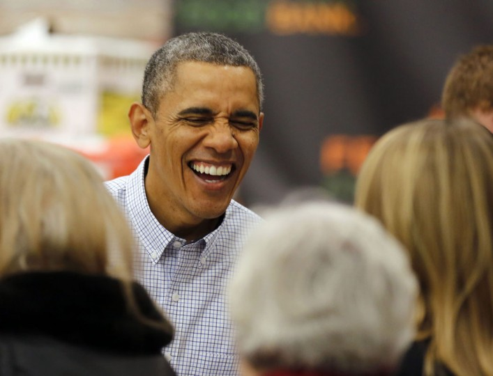 U.S. President Barack Obama smiles as he hands out Thanksgiving food at the Capital Area Food Bank in Washington, November 27, 2013. (REUTERS/Larry Downing)