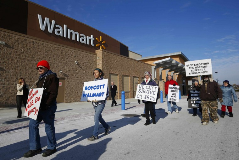 A group of protesters walk through the Walmart retail store parking lot on Black Friday in Elgin, Illinois, November 29, 2013. The group is part of a national campaign against the low wages they say Walmart pays its employees, according to the protesters. (Jeff Haynes/REUTERS)