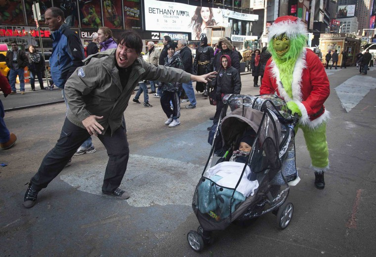 "A man (R) dressed up as ""the Grinch"", a fictional character by author Dr. Seuss, who poses for photos with people for money, poses for a picture with a baby in a stroller and his father in Times Square, during Black Friday sales in New York November 29, 2013. Black Friday, the day following Thanksgiving Day holiday, has traditionally been the busiest shopping day in the United States. (Carlo Allegri/REUTERS)"