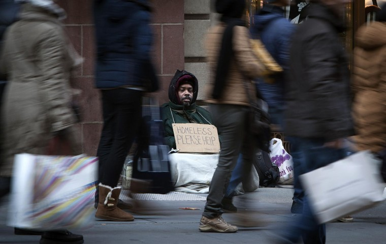 A man who says he is homeless sits on 5th Ave. as shoppers pass, looking for Black Friday sales, in New York November 29, 2013. Black Friday, the day following Thanksgiving Day holiday, has traditionally been the busiest shopping day in the United States. (Carlo Allegri/REUTERS)