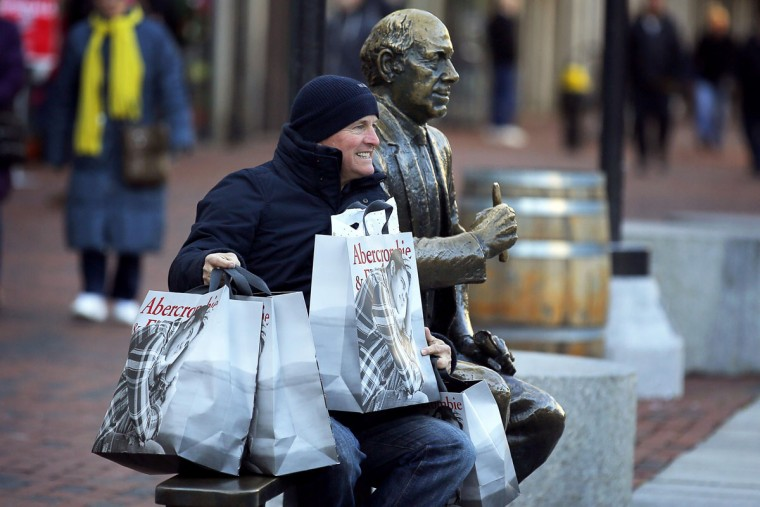 A man poses for a photograph with his shopping bags and a statue of hall of fame Boston Celtics coach Red Auerbach on Black Friday in Boston, Massachusetts November 29, 2013. Black Friday, the day following the Thanksgiving Day holiday, has traditionally been the busiest shopping day in the United States. (Brian Snyder/REUTERS)