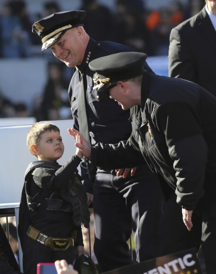 "Five-year-old leukemia survivor Miles Scott, dressed as ""Batkid"" high fives with San Francisco Fire Department chief Joanne Hayes-White (R) as with police chief Greg Suhr (C) watches during a ceremony as part of a day arranged by the Make- A - Wish Foundation in San Francisco, California November 15, 2013. The young cancer survivor was treated to various super hero scenarios including receiving a commendation at San Francisco City Hall. (Robert Galbraith/Reuters)"