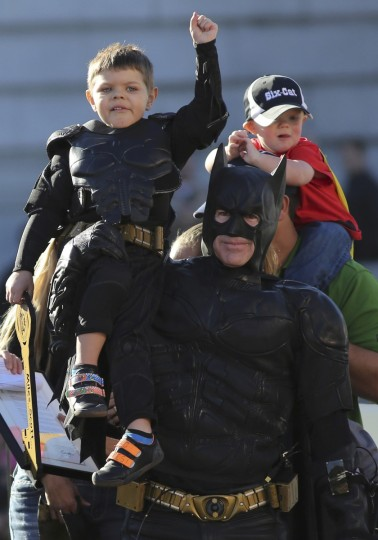 "Five-year-old leukemia survivor Miles Scott, dressed as ""Batkid"" waves to crowd on the shoulders of Batman during a ceremony as part of a day arranged by the Make- A - Wish Foundation in San Francisco, California November 15, 2013. Miles brother Clayton (R) sits on the shoulders of his father Nick (R). The young cancer survivor was treated to various super hero scenarios including receiving a commendation at San Francisco City Hall. (Robert Galbraith/Reuters)"