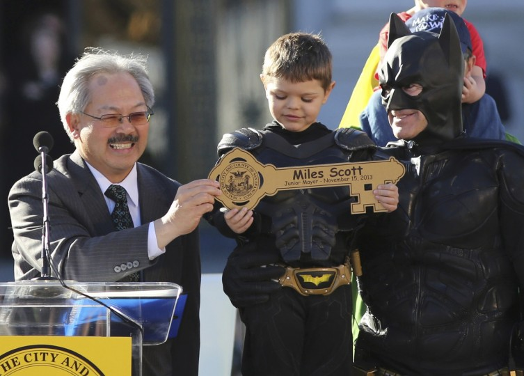 "Five-year-old leukemia survivor Miles Scott, dressed as ""Batkid"" receive a key to the city declaring him ""Junior Mayor"" from San Francisco Mayor Ed Lee (L) during a ceremony as part of a day arranged by the Make- A - Wish Foundation in San Francisco, California November 15, 2013. The young cancer survivor was treated to various super hero scenarios including receiving a commendation at San Francisco City Hall. (Robert Galbraith/Reuters)"