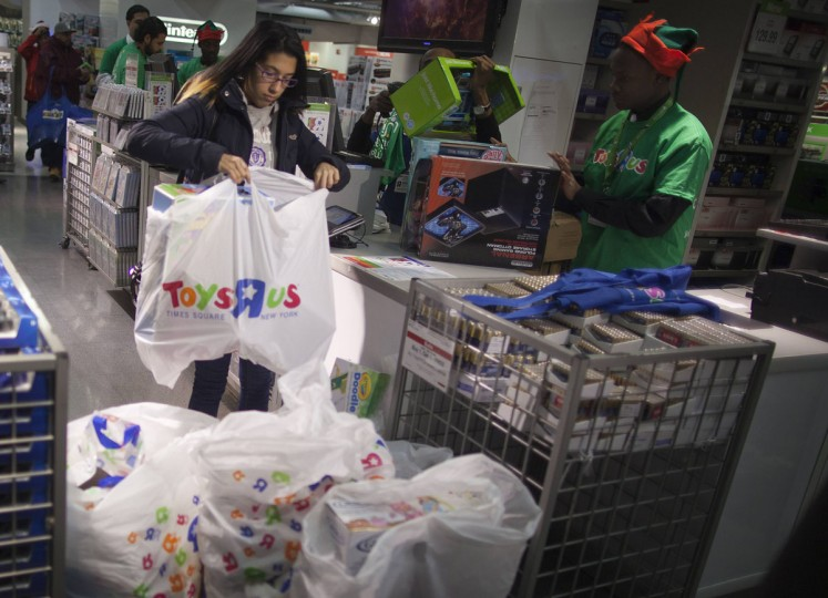 """A woman piles up her purchases at a Toys""""R""""Us store during their Black Friday Sale in New York November 28, 2013. (Carlo Allegri/REUTERS)"""