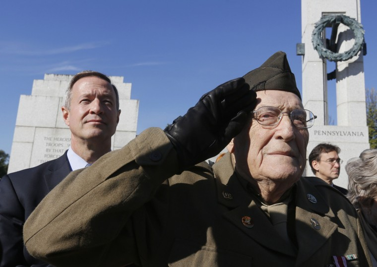 World War Two veteran Anthony Gizzi, 90, of Haverstraw, New York, salutes next to Maryland Governor Martin O'Malley (L) while honoring his fallen comrades at the World War Two Memorial on Veteran's Day in Washington, November 11, 2013. (Larry Downing/Reuters)