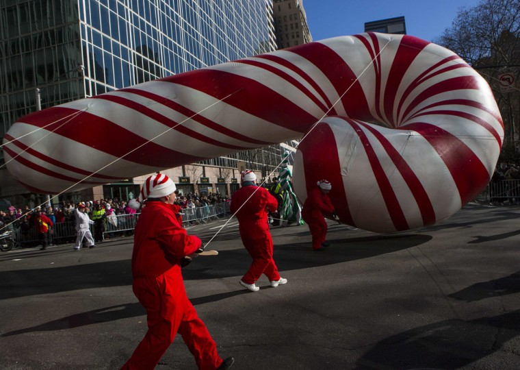 Handlers try to control a candy cane balloon as the wind blows it over on Sixth Avenue during the 87th Macy's Thanksgiving Day Parade in New York. (REUTERS/Eric Thayer)
