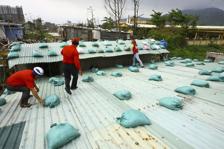 Red Cross volunteers and staff place sandbags on houses in Hoa Hai ward, Ngu Hanh Son district, Da Nang, ahead of Typhoon Haiyan's expected landfall November 9, 2013, in this handout photo provided by VNRC. Typhoon Haiyan, which has killed at least 100 people in Philippines, was heading for Vietnam late on Saturday and authorities in 15 provinces in Vietnam have started to call back boats and prepare for possible landslides. Nearly 300,000 people were moved to safer areas in two provinces alone - Da Nang and Quang Nam - according to the government's website. (Tran Quang Tuan/VNRC/REUTERS)