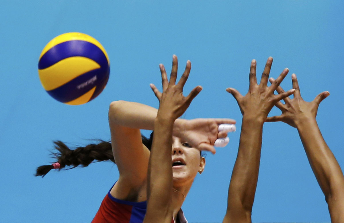 Natalia Malykh (L) of Russia spikes the ball against Brazil during their FIVB Women's Volleyball Grand Champions Cup 2013 in Tokyo November 16, 2013. (Toru Hanai/REUTERS)
