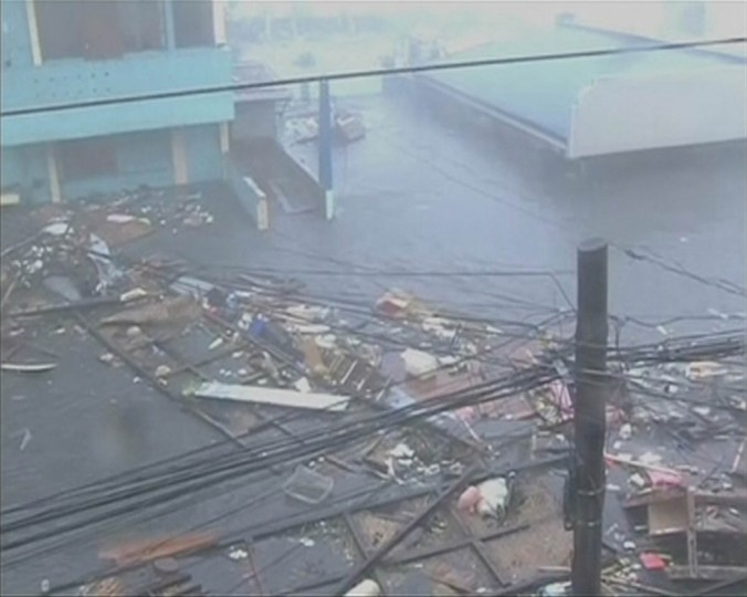 Debris floats on a flooded road as strong winds and rain continue to batter buildings after Typhoon Haiyan hit Tacloban city, Leyte province in this still image from video November 8, 2013. Haiyan, potentially the strongest recorded typhoon to make landfall, slammed into the Philippines' central islands on Friday, forcing millions of people to flee to safer ground or take refuge in storm shelters. The category-five super typhoon whipped up giant waves as high as 4-5 metres (12-15 feet) that lashed the islands of Leyte and Samar, and was on track to carve a path through popular holiday destinations. (Reuters TV)