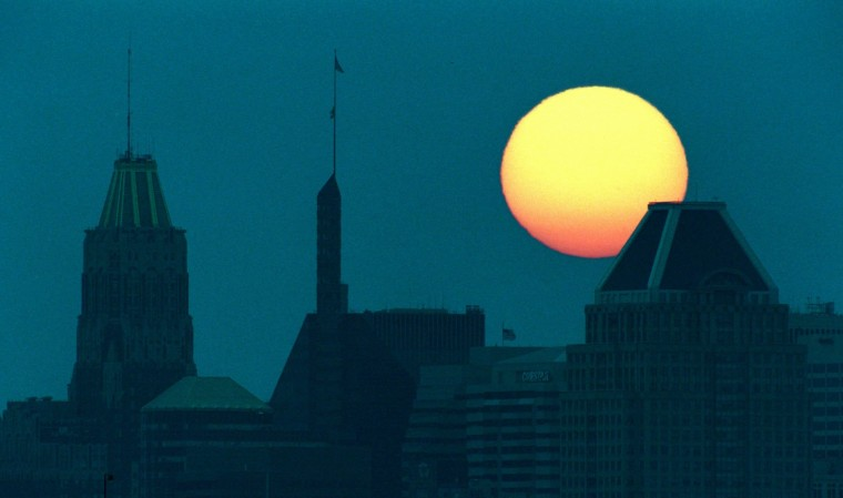 Baltimore's skyline is silhoutted by a setting sun on a day that saw temperatures climb into the upper 90's with high humidity. (Doug Kapustin/Baltimore Sun Photo/July 21, 1998)