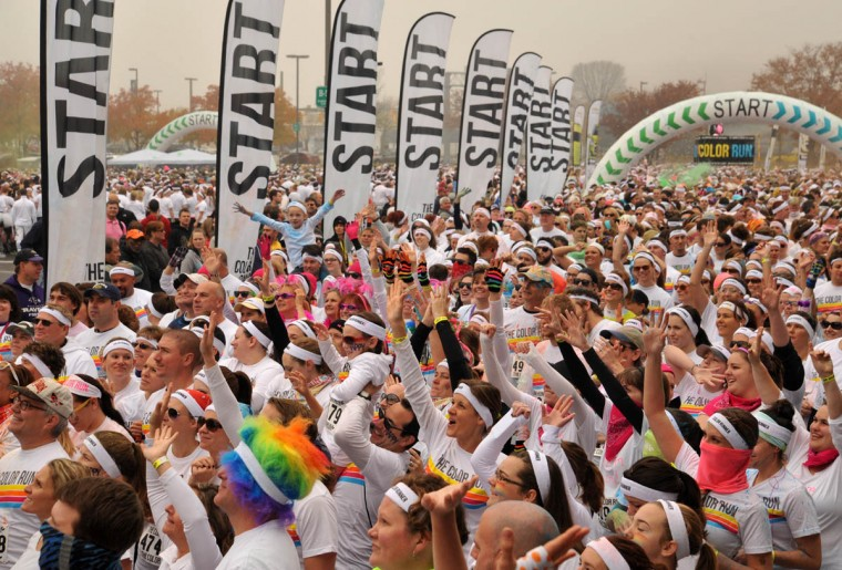 "Runners get psyched at the start of the morning Color Run. About 10,000 people participated in each of two 5k Color Runs today, in which they were doused with colored powders along the route. BIlled as the ""Happiest 5k on the Planet,"" The Color Run is operated by a for-profit management company, with partnerships with local charities. (Amy Davis /Baltimore Sun)"