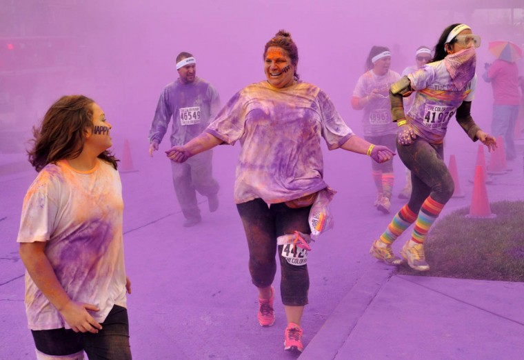 "Outside M&T Stadium, home of the Ravens, the color sprayed on runners was purple, of course. About 10,000 people participated in each of two 5k Color Runs today, in which they were doused with colored powders along the route. BIlled as the ""Happiest 5k on the Planet,"" The Color Run is operated by a for-profit management company, with partnerships with local charities. (Amy Davis /Baltimore Sun)"