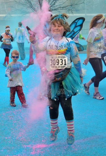 Katie Gaff of Middle River, wearing butterfly wings, flew through a blue and pink cloud in the morning Color Run. (Amy Davis /Baltimore Sun)