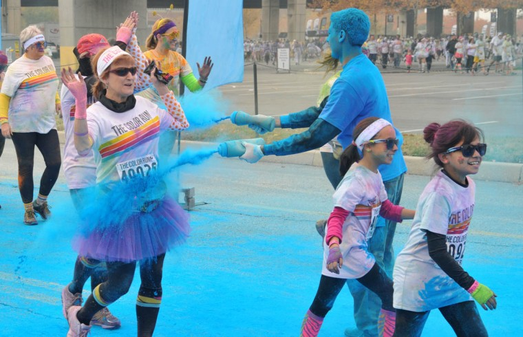 Volunteers sprayed the runners with their final color, blue, in the morning Color Run. (Amy Davis /Baltimore Sun)