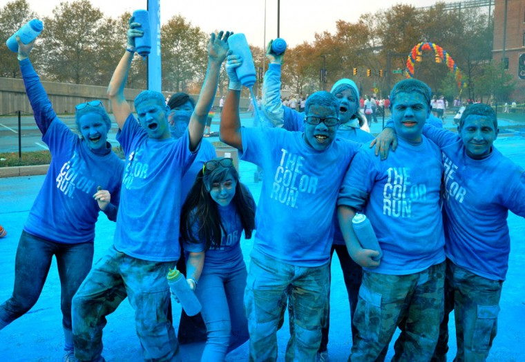 "Impromptu group portrait of the volunteers spraying blue powder near the end of the morning Color Run. About 10,000 people participated in each of two 5k Color Runs today, in which they were doused with colored powders along the route. BIlled as the ""Happiest 5k on the Planet,"" The Color Run is operated by a for-profit management company, with partnerships with local charities. (Amy Davis /Baltimore Sun)"