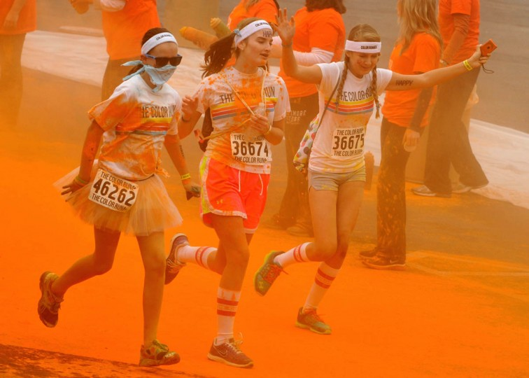 Girls run through Orioles orange near Camden Yards in the morning Color Run. (Amy Davis / The Baltimore Sun)