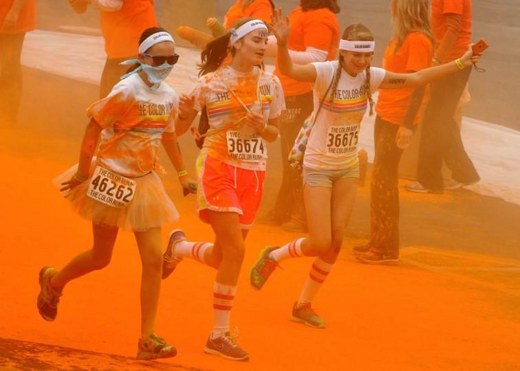 Girls run through Orioles orange near Camden Yards in the morning Color Run. (Amy Davis / The Baltimore Sun)