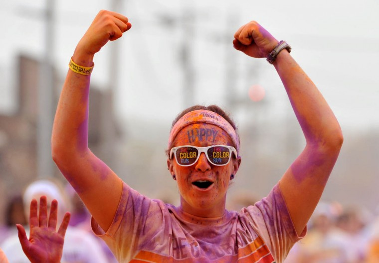 "A happy runner anointed in orange and purple powder midway through the morning Color Run. About 10,000 people participated in each of two 5k Color Runs today, in which they were doused with colored powders along the route. BIlled as the ""Happiest 5k on the Planet,"" The Color Run is operated by a for-profit management company, with partnerships with local charities. (Amy Davis / The Baltimore Sun)"