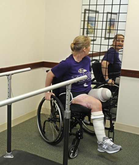Erika Brannock, who was injured in the Boston Marathon bombing, tries her new prosthetic leg for the first time at Dankmeyer Orthotics and Prosthetics. She looks in a mirror in the prosthetic fitting room. (Barbara Haddock Taylor/Baltimore Sun)