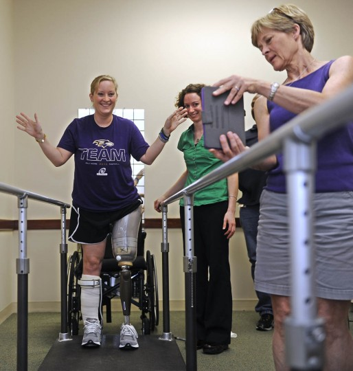 "Erika Brannock smiles as she stands with no hands holding the railing. She tried her new prosthetic leg for the first time at Dankmeyer Orthotics and Prosthetics, where her mother, Carol Downing, recorded the event ""live"" so relatives in other states could share the moment. Angie Swindell, the certified prosthetist and orthotist who made Erika's prosthetic leg, stands in center. (Barbara Haddock Taylor/Baltimore Sun)"