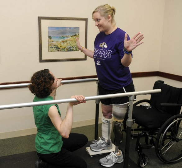 """Erika Brannock looks happy about standing up, """"no hands,"""" for the first time. Prosthetist Angela Swindell is on left. (Barbara Haddock Taylor/Baltimore Sun)"""