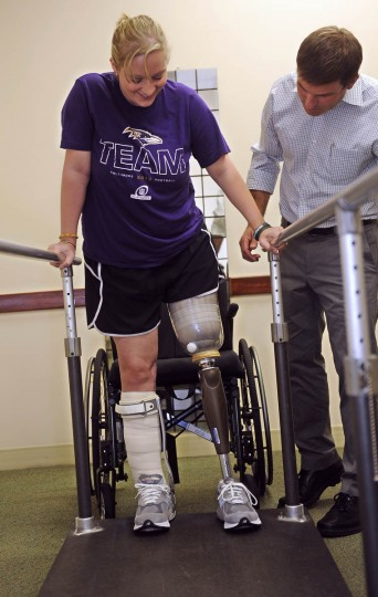 Erika Brannock, who was injured in the Boston Marathon bombing, smiles as she tries her new prosthetic leg for the first time today at Dankmeyer Orthotics and Prosthetics. Mark Hopkins, the Clinical Director at Dankmeyer, is on right. (Barbara Haddock Taylor/Baltimore Sun)