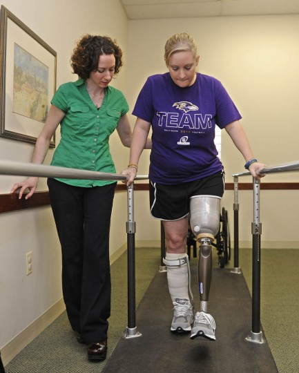 Erika Brannock takes a few tentative first steps with Angela Swindell, left, a certified prothestist and orthotist who made the leg. (Barbara Haddock Taylor/Baltimore Sun)