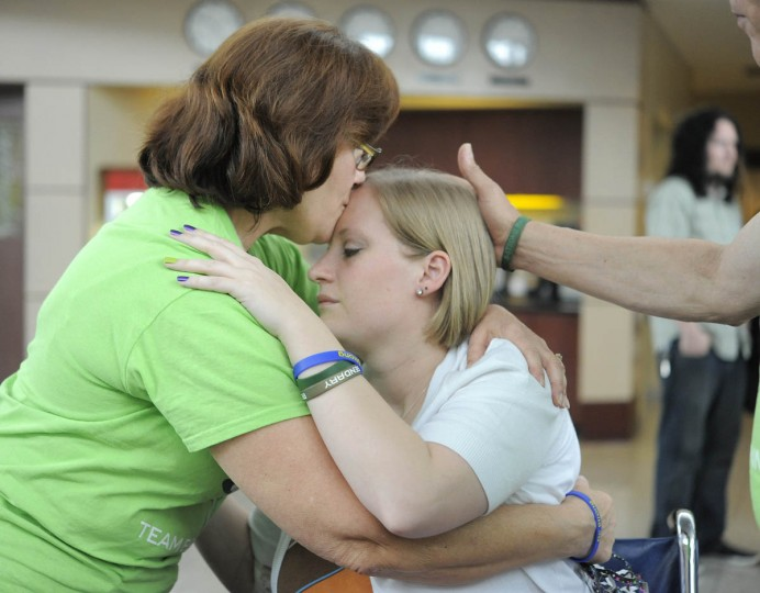 """Boston bombing victim Erika Brannock gets a kiss from her """"Aunt Debbie,"""" Deborah Atkinson, as she returns home to Baltimore after seven weeks in the hospital. She is greeted by friends and family at Signature Aviation. (Lloyd Fox/Baltimore Sun)"""