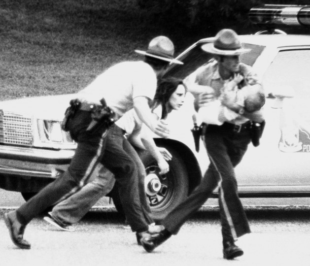 8/11/1979 - Ellicott City, MD - Two Howard County police officers shield a young woman and her baby as they escape a gunman who held the two hostage in an Ellicott City apartment for several hours after he and the woman argued about custody of the child. (Weyman Swagger/Baltimore Sun)