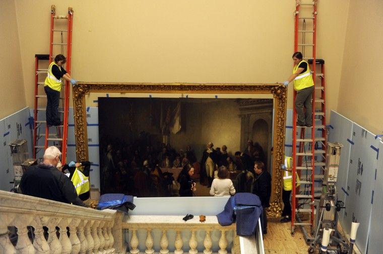 Professional art handlers from Artex remove the 1859 painting of George Washington resigning his commission from the main stairwell at the State House. It will be restored over the course of a year and then re-installed. Here, senior art handler Lisa Border, left, and Hannah Thresher, right, steady the frame from ladders as it is lowered. (Barbara Haddock Taylor/Baltimore Sun)