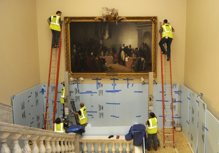Art handlers from Artex spent most of a day removing and packing the 1859 painting of George Washington resigning his commission from the main stairwell at the State House. Here, they prepare the painting for being taken down slowly with the help of cranes. The painting will be restored over the course of a year and then re-installed. The marble walls and banisters are protected by styrofoam sheets and padding during the operation. (Barbara Haddock Taylor/Baltimore Sun)