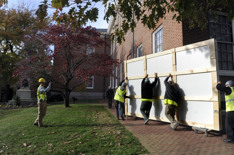 Professional art handlers remove the giant painting of George Washington. Because of the painting's size, it had to be removed through one of the first floor windows The painting will be restored over the course of a year and then re-installed. (Barbara Haddock Taylor/Baltimore Sun)