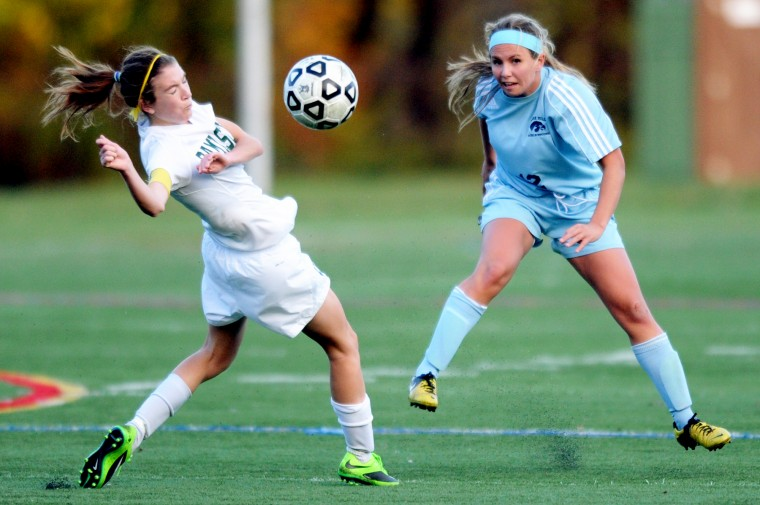 Damascus's Annika Leiby, left, twists her body to avoid getting hit by a shot from River Hill's Shannon Filippone during the girls soccer 3A state semifinal match at the CCBC-Essex campus in Rosedale on Saturday, Nov. 9, 2013. (Jon Sham/BSMG)