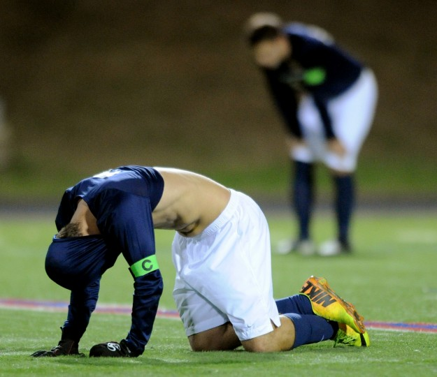 River Hill's Zach Riso falls to the ground and covers his head with his jersey as he and teammates lament their loss to Urbana in the 3A state semifinal soccer match at the CCBC-Essex campus in Rosedale on Saturday, Nov. 9, 2013 (Jon Sham/BSMG)