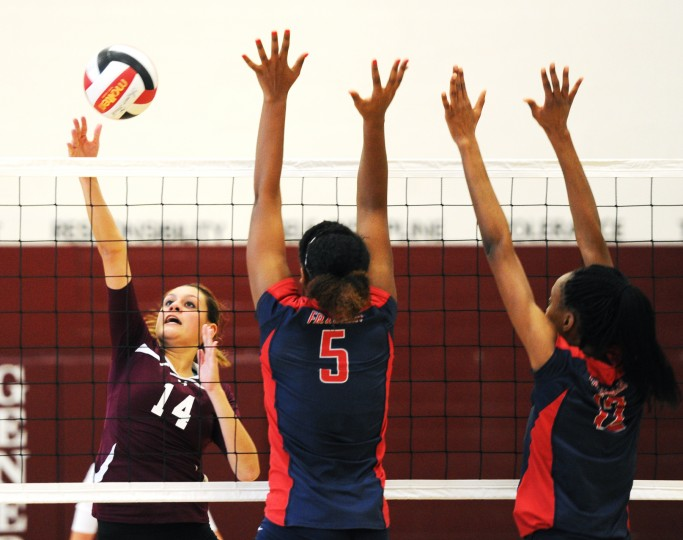 Towson's Sabrina Nance, left, lofts the ball over the net as Franklin's Kiana Durant, center, and Whisper Fisher go up to meet her with a block during the regional semifinal volleyball match at Towson High School on Wednesday, Nov. 6, 2013. (Jon Sham/BSMG)