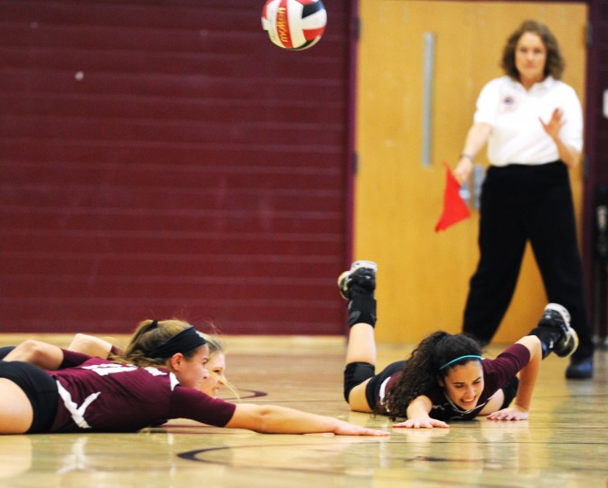 Towson players sprawl out on the floor to get to the ball, but all three miss during the regional semifinal volleyball match at Towson High School on Wednesday, Nov. 6, 2013. (Jon Sham/BSMG)