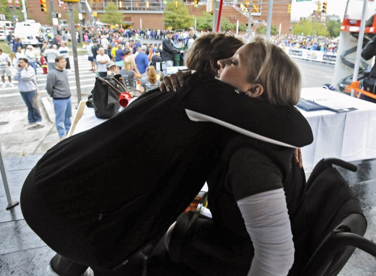 Honorary starter Erika Brannock, right, a survivor of the Boston Marathon terrorist bombing attack, gets a hug from mother Carol Downing, left, before starting the 2013 Baltimore Marathon. (Kenneth K. Lam/Baltimore Sun)