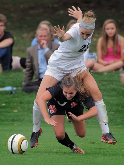 Archbishop Spalding forward/midfielder Colby Snyder stumbles as McDonogh forward Anna Bialczak clambers over her back. (Karl Merton Ferron/Baltimore Sun)