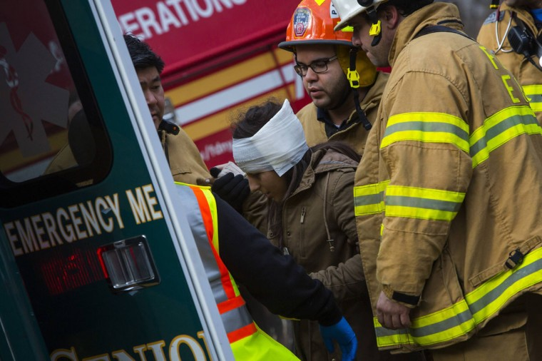 A woman is taken to an ambulance at the site of a Metro-North train derailment in the Bronx borough of New York December 1, 2013. At least four people were killed and 63 injured, including 11 critically, when the suburban train derailed, with at least five cars from the Metro-North train sliding off the tracks, officials said. (Eric Thayer/Reuters)