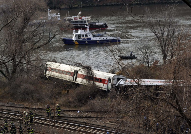 Emergency workers at the scene of a commuter train wreck on Dec 1, 2013 in the Bronx borough of New York. The train bound for New York's Grand Central Station derailed in the Bronx Sunday with at least four people reported dead after several rail cars left the tracks near the Spuyten Duyvil railroad station. The southbound train was traveling from Poughkeepsie to Grand Central Terminal when the accident occurred. (Timothy Clary/AFP/Getty Images)