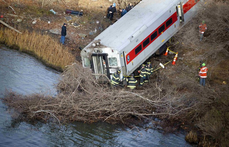 Emergency workers examine the site of a Metro-North train derailment in the Bronx borough of New York December 1, 2013. At least four people were killed and 63 injured, including 11 critically, when the suburban train derailed, with at least five cars from the Metro-North train sliding off the tracks, officials said. (Carlo Allegri/Reuters)