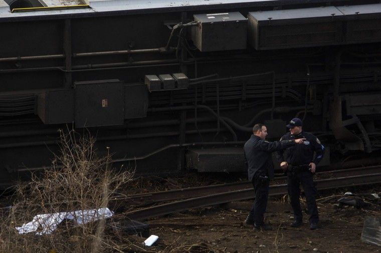 Emergency workers stand near the the site of a Metro-North train derailment in the Bronx borough of New York December 1, 2013. At least four people were killed and 63 injured, including 11 critically, when the suburban train derailed, with at least five cars from the Metro-North train sliding off the tracks, officials said. (Eric Thayer/Reuters)