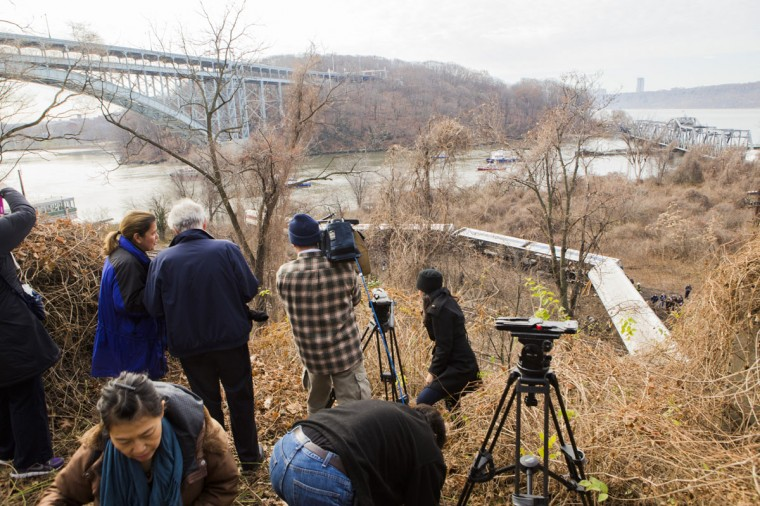Onlookers and media watch after Metro-North train derailed near the Spuyten Duyvil station December 1, 2013 in the Bronx borough of New York City. Multiple injuries and several deaths were reported after the seven car train left the tracks as it was heading to Grand Central Terminal along the Hudson River line. (Christopher Gregory/Getty Images)